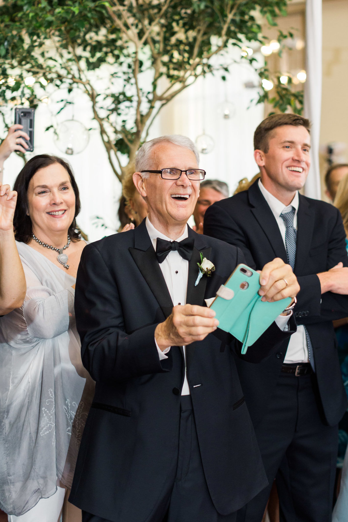 The father of the groom stood in awe as he videoed his wife doing a choreographed surprise dance planned just moments prior. Photo by luxury destination wedding photographer Rebecca Cerasani.