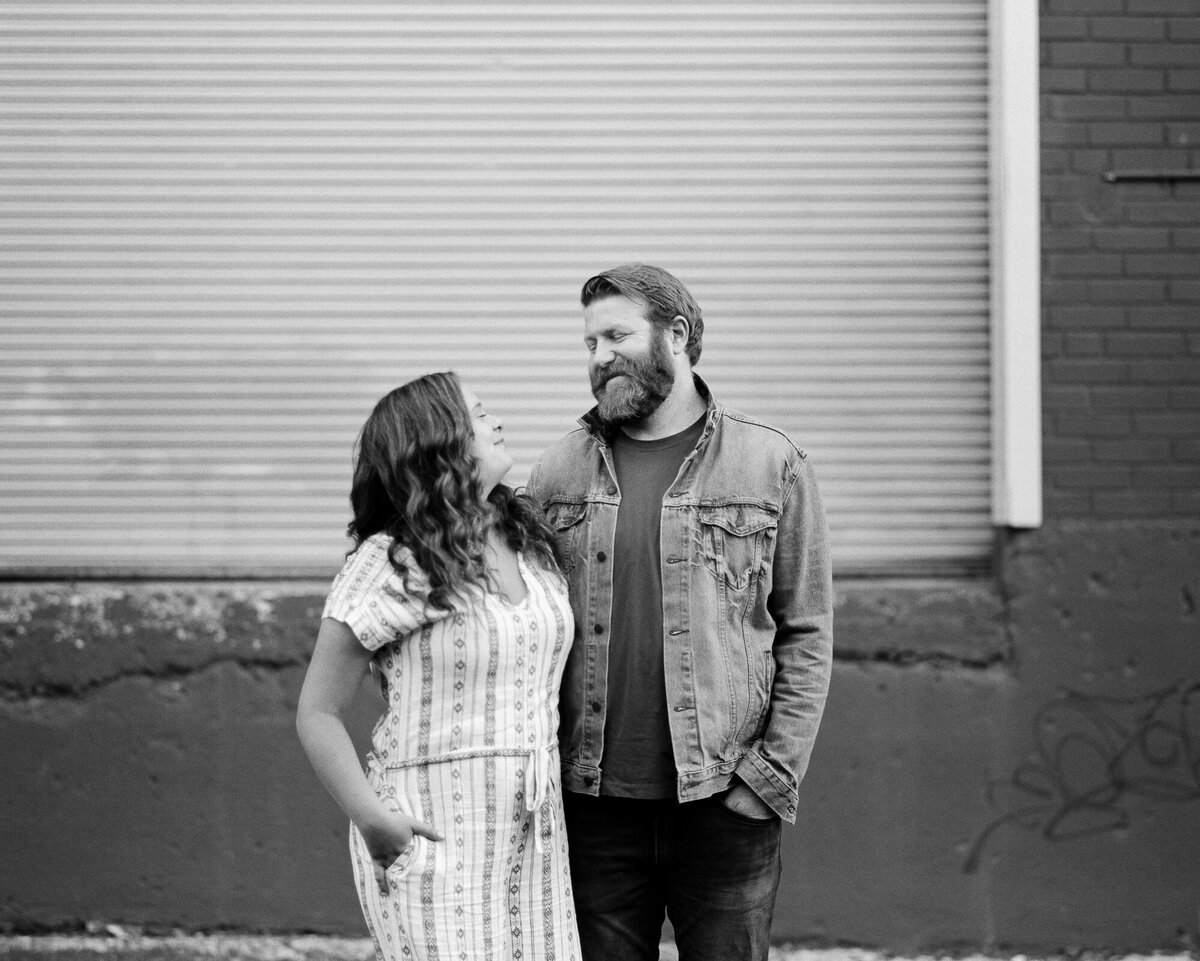 Couple poses in front of garage doors for engagement photos on film