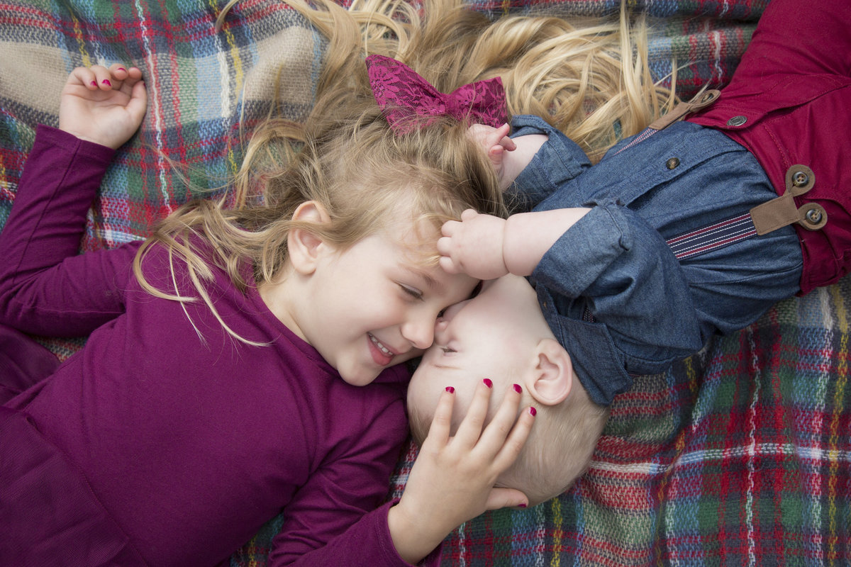 siblings cuddle on ground at sioux rec