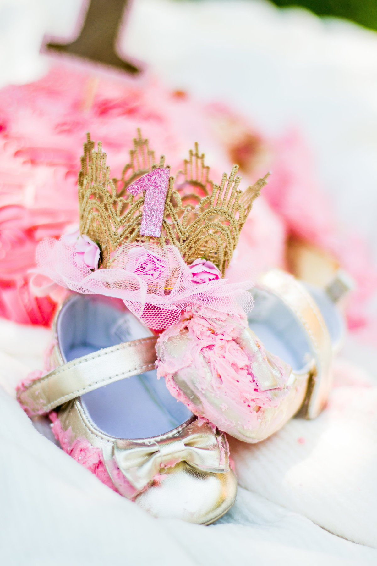 Gold and pink birthday, smash cake one-year old, girl, Garaman Park, Jackson, WY, baby crown, cake, mess, gold baby shoes