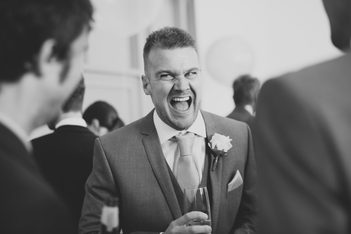 best man talking with his friends and laughing when drinking champagne