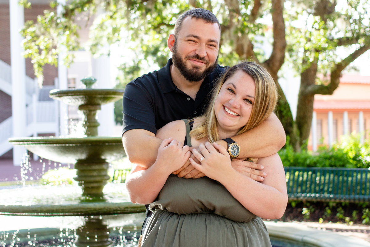 Couple giggles and hugs during their engagement photo session in Celebration, Florida