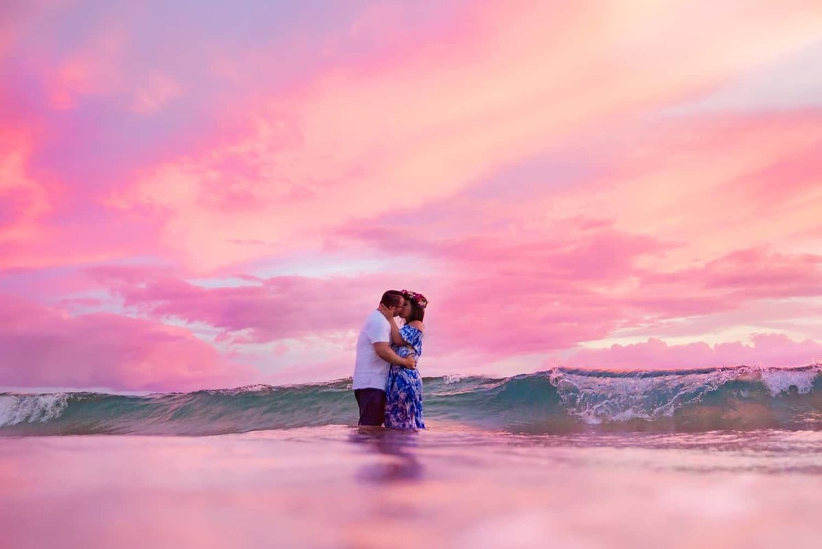 Couple kissing in breaking waves on Maui