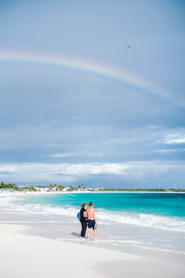 couple standing under a rainbow on the beach in anguilla