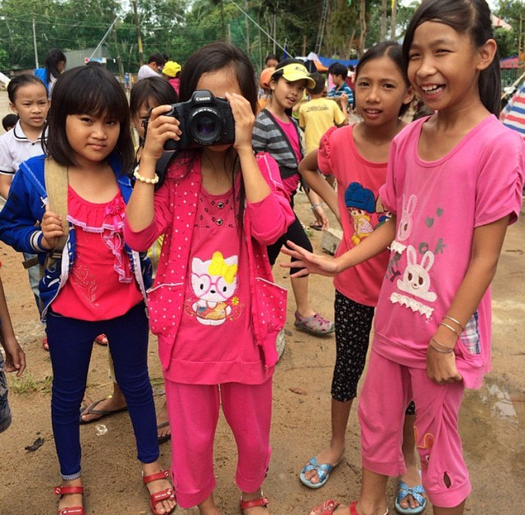 Young Vietnamese girl holds camera while other girls look on in Duc Linh, Vietnam.