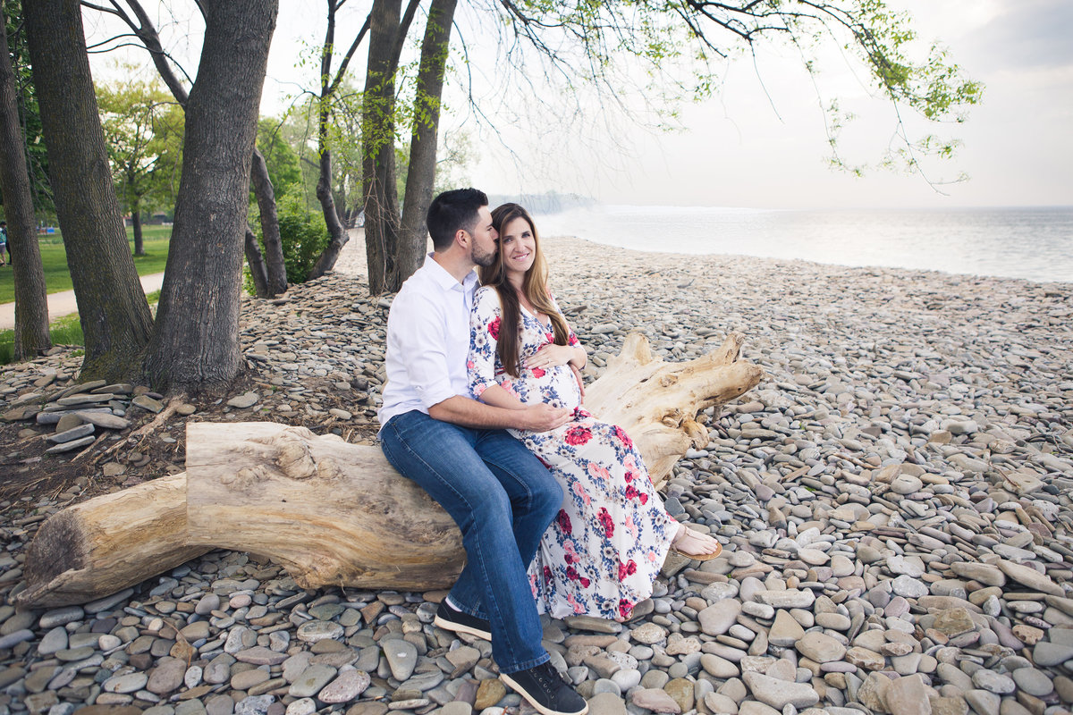 pregnant couple sitting on log by lakefront {Milton Maternity Photographer}