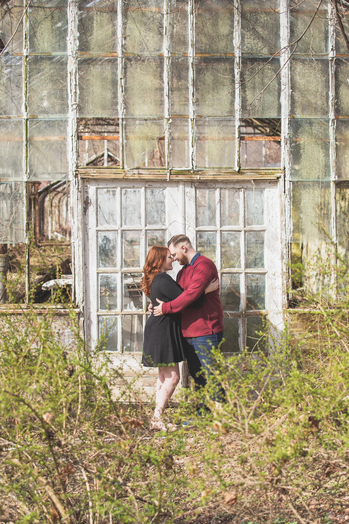 Engaged couple standing by old greenhouse