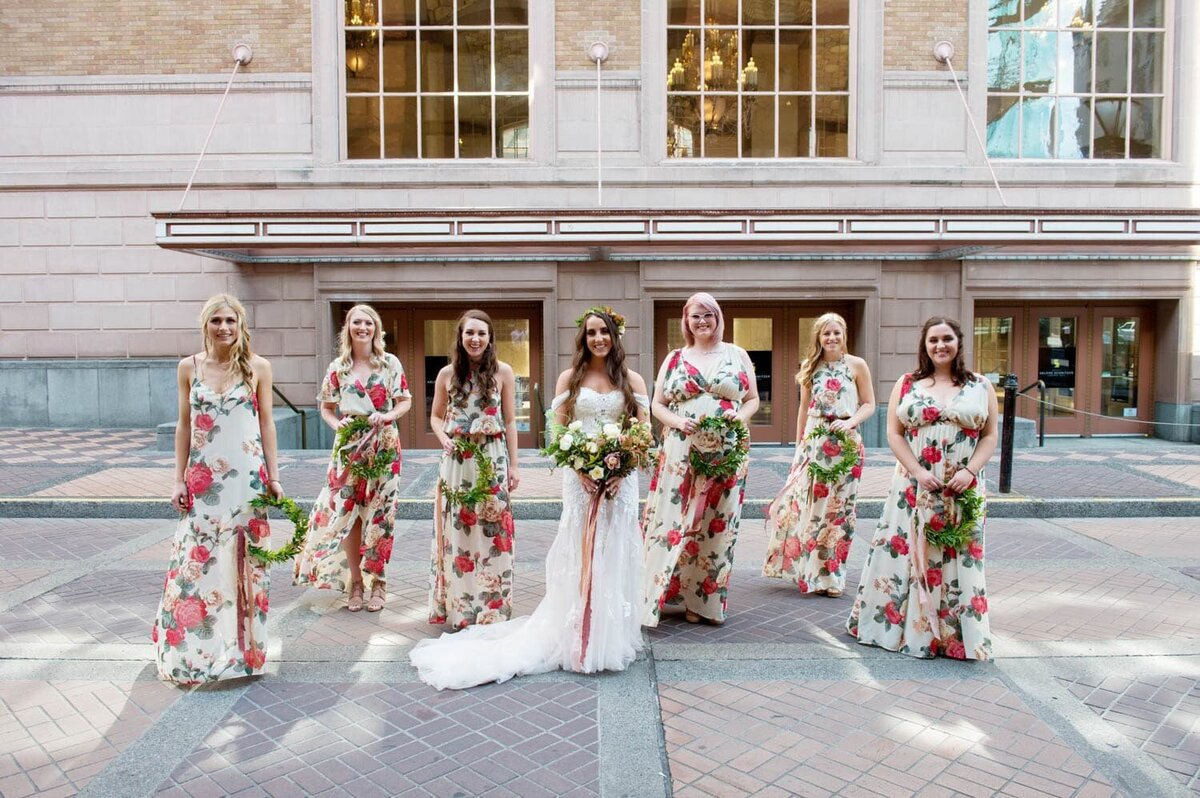 a bride stands in the middle of 6 bridesmaids wearing colorful floral bridesmaid dresses