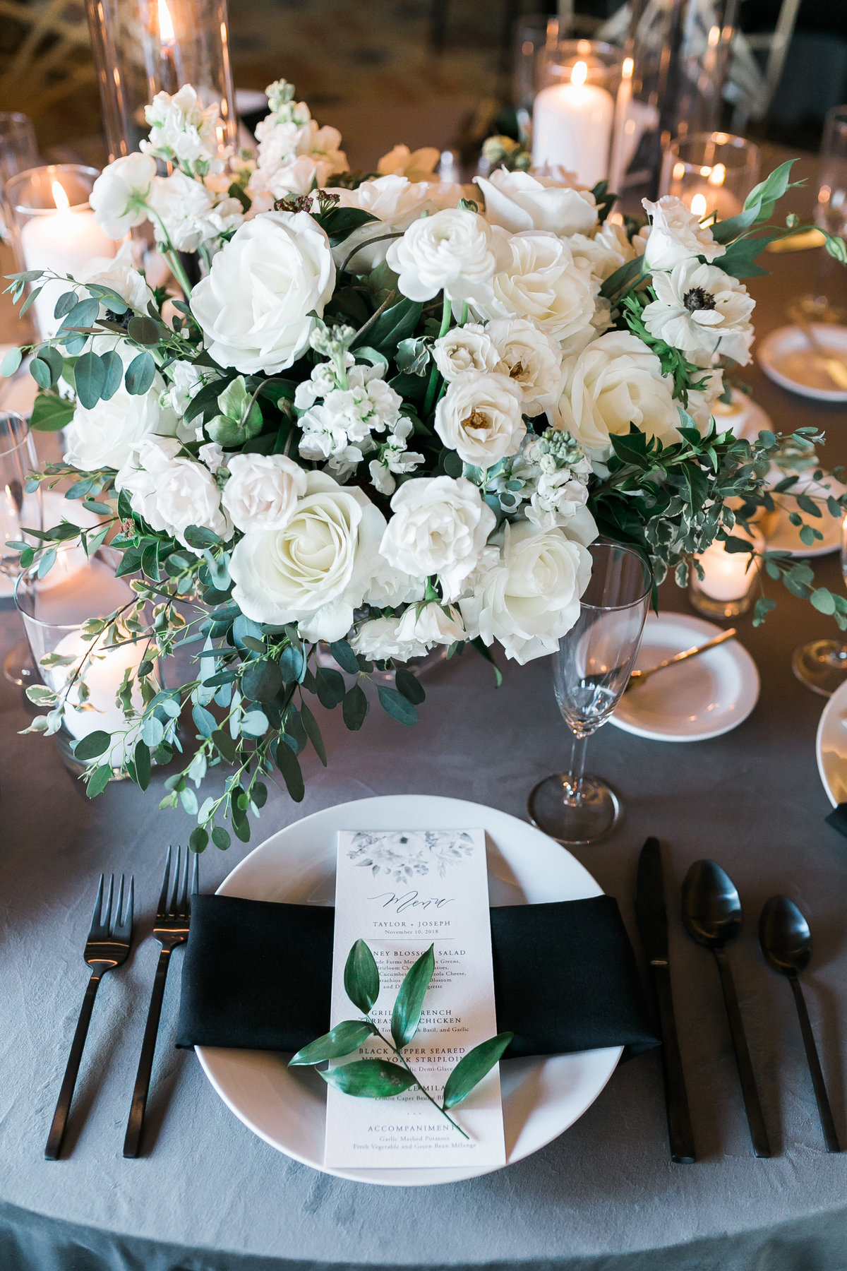 wedding tablescape with grey velvet linen and  black flatware with white and green floral centerpiece