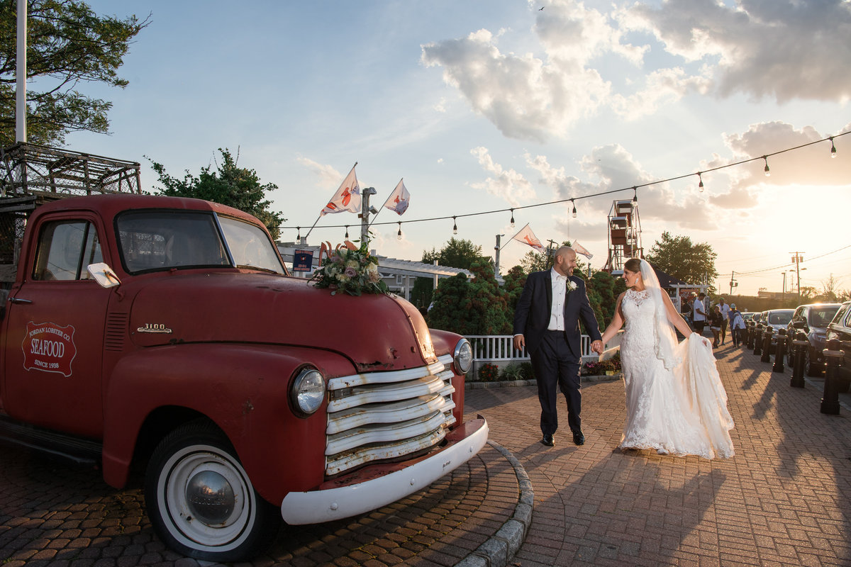 wedding photo of bride and groom holding hands and walking near red truck at The Loft by Bridgeview