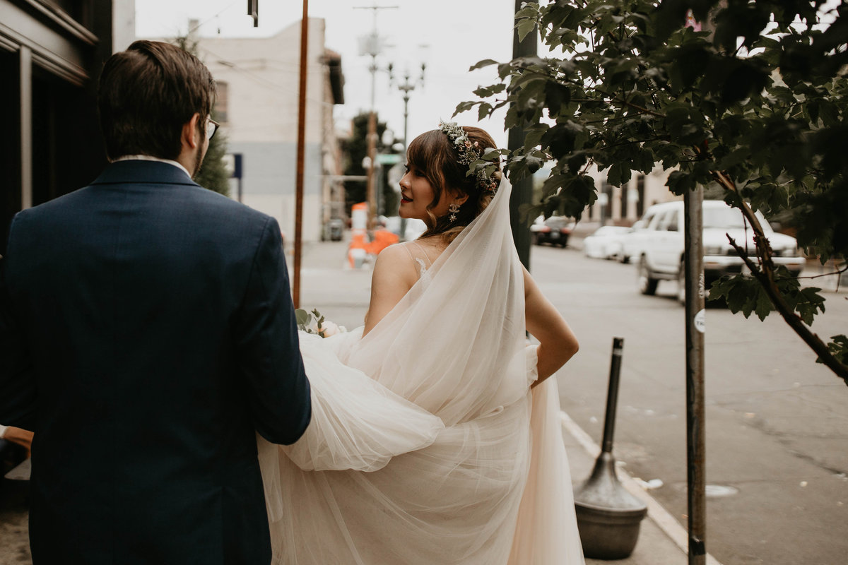 Groom carries his brides veil as she looks back at him on their wedding day