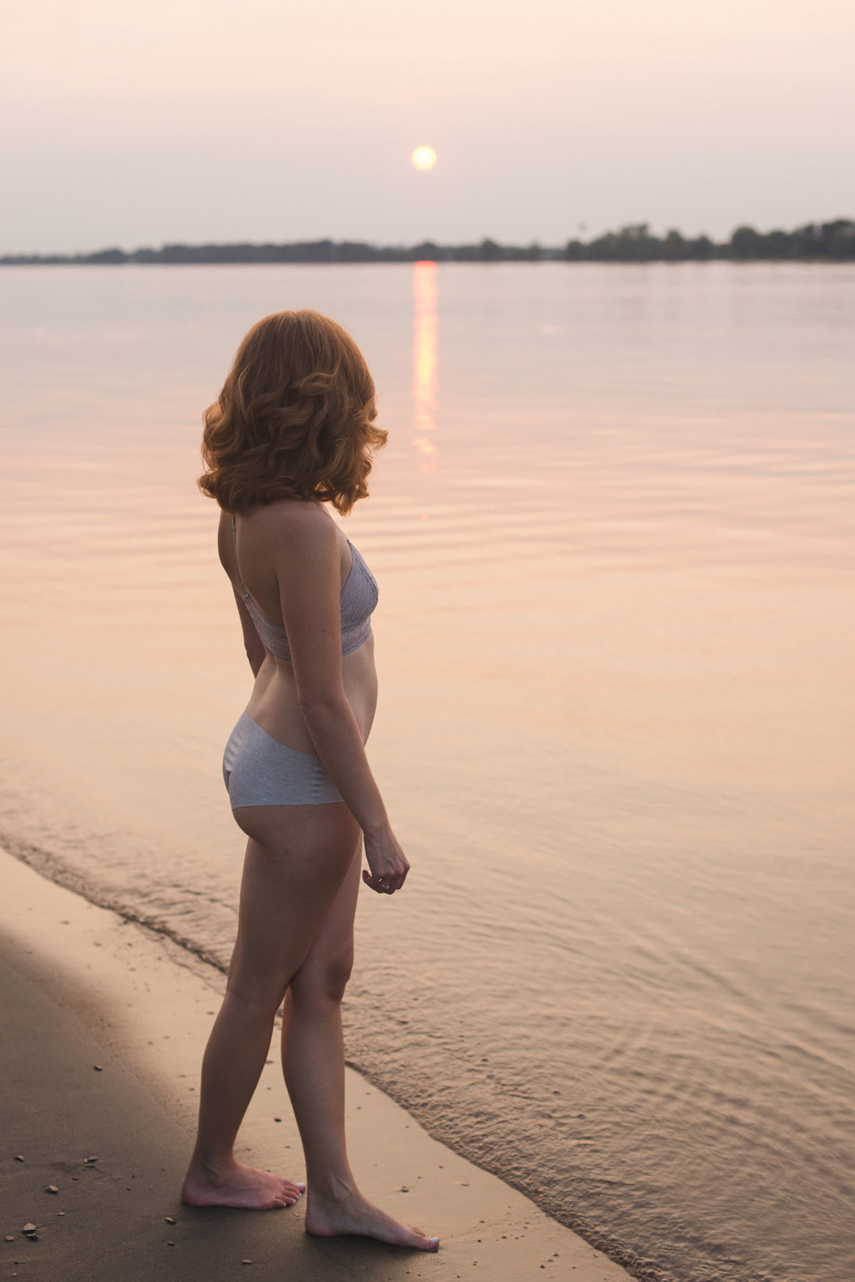 red headed girl standing by the water's edge in her underwear looking out at the sunset