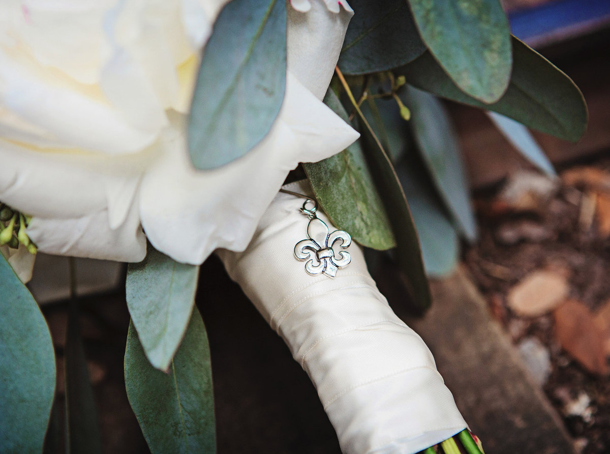fleur de lis charm on a wedding bouquet sitting on the railroad tracks in City Park New Orleans