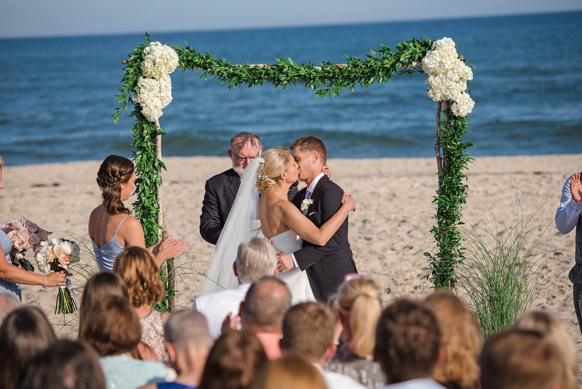 First kiss as husband and wife during a beach ceremony