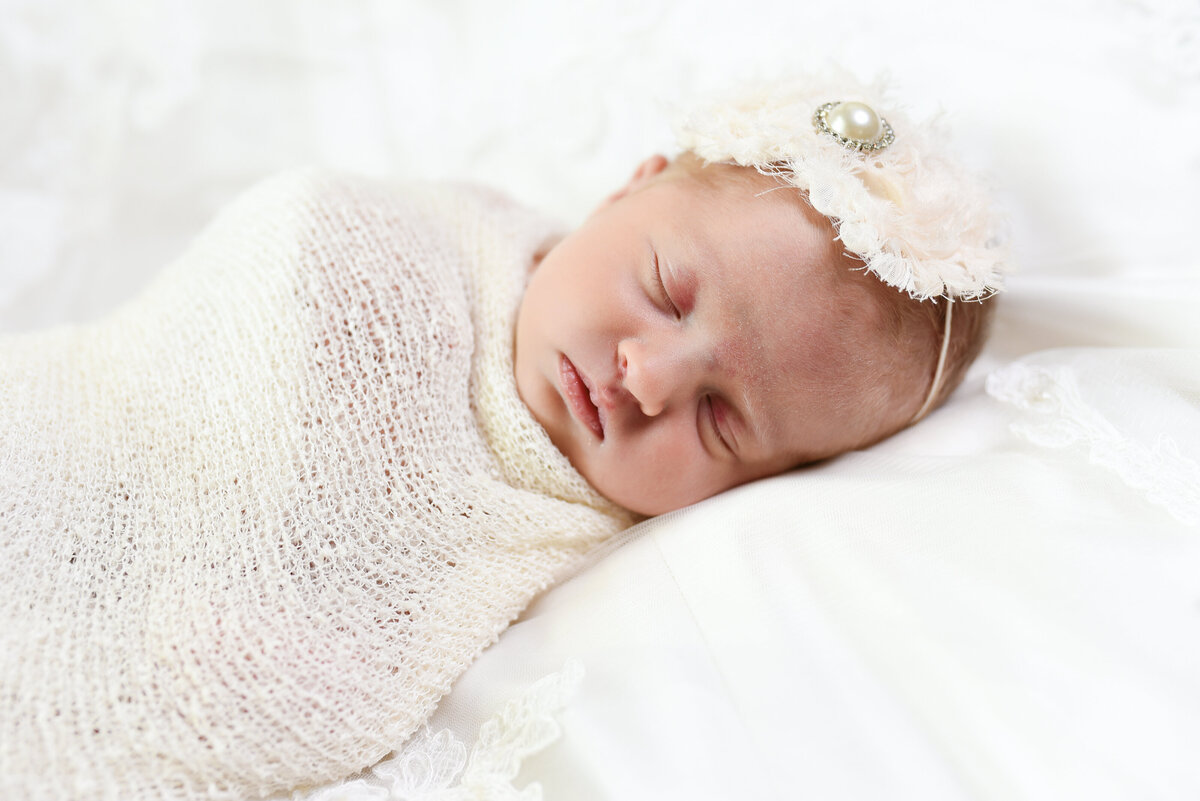 Beautiful Mississippi newborn photography: Baby girl wrapped in white with rhinestone headband on mom's wedding gown