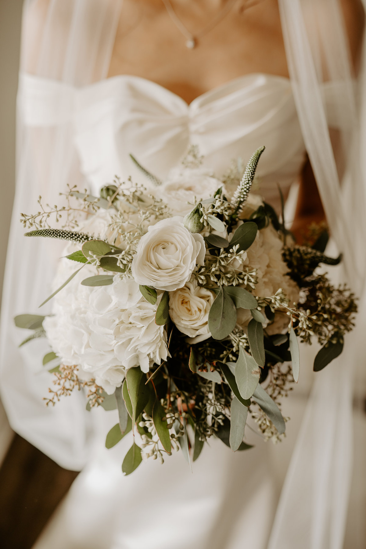 bouquet in front of wedding dress