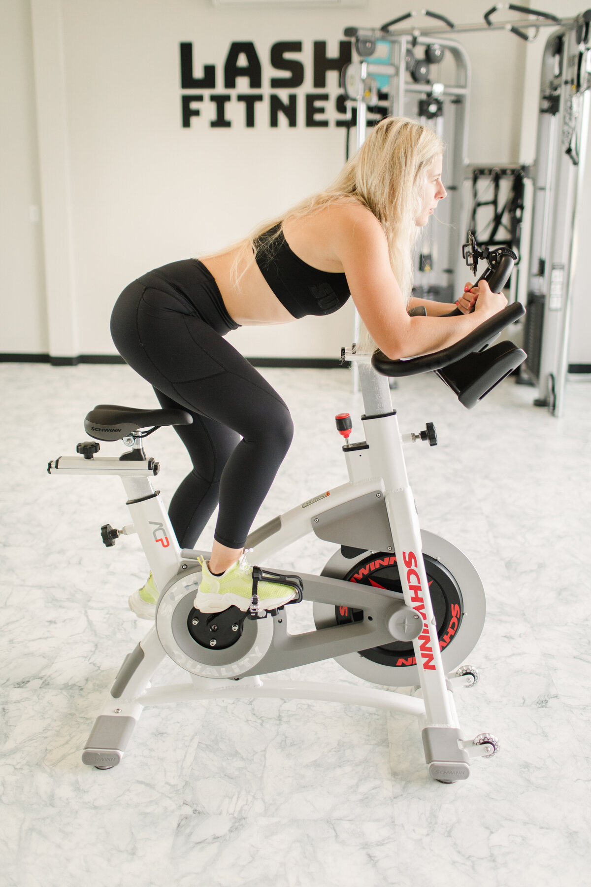 young blonde woman on a stationary bike leading a cycling class