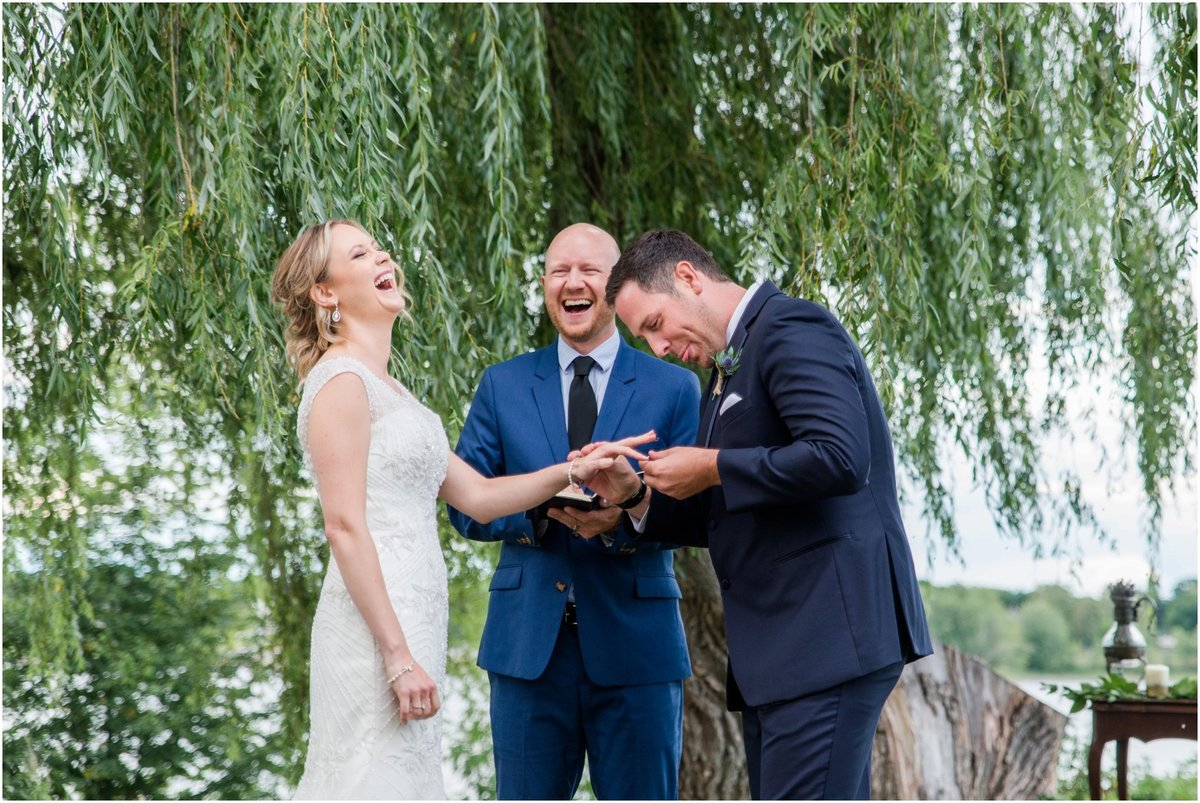 Bride and groom exchanging rings in front of a willow tree