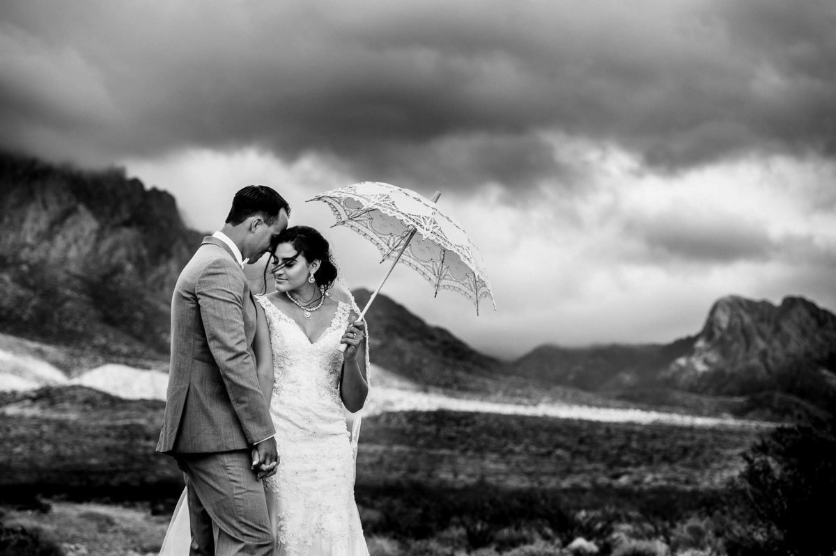 bride and groom portrait at organ mountains in las cruces holding a white umbrella  by stephane lemaire photography