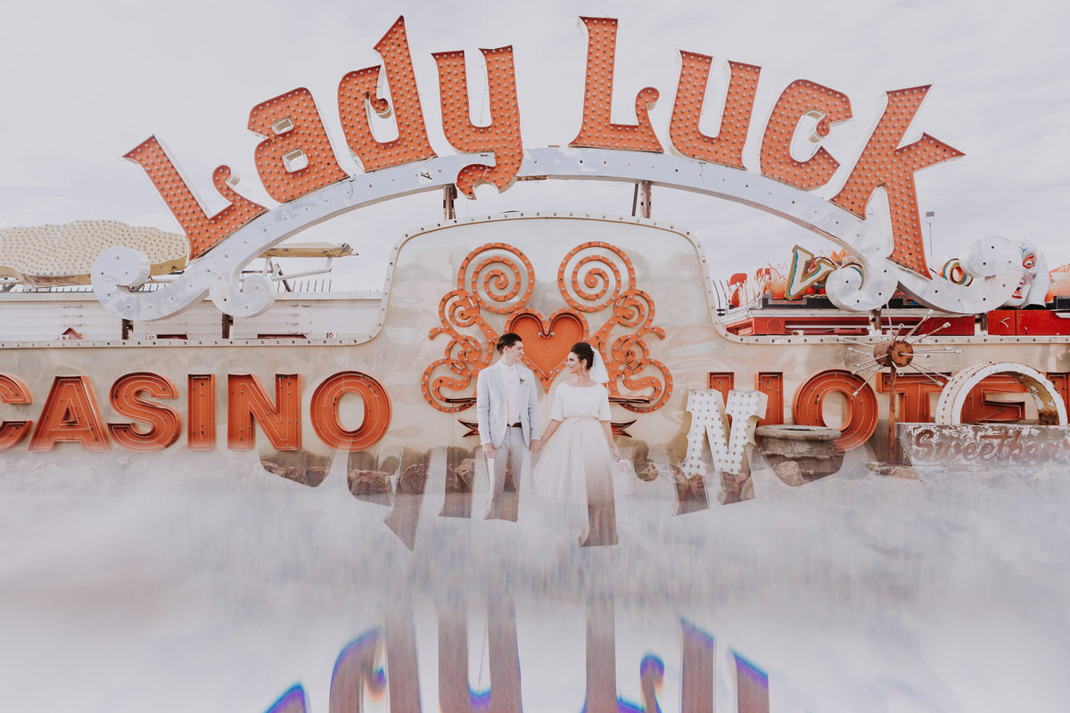 Neon Museum wedding photographers las vegas couple poses in front of iconic lady luck sign