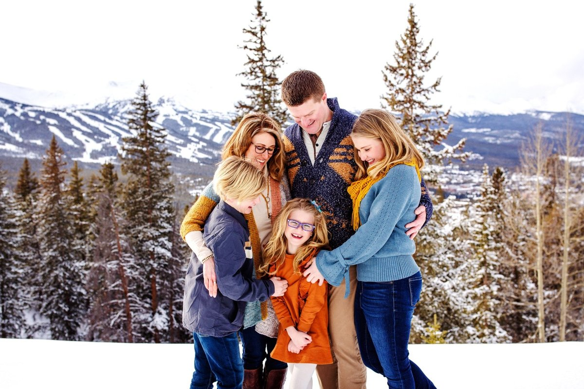Family group hug in the snowy mountains
