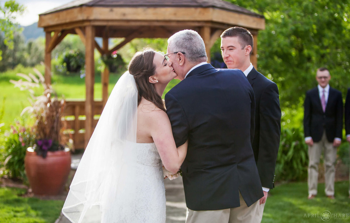 Sweet Colorado wedding photo of bride kissing her dad at Denver Botanic Gardens Chatfield Farms
