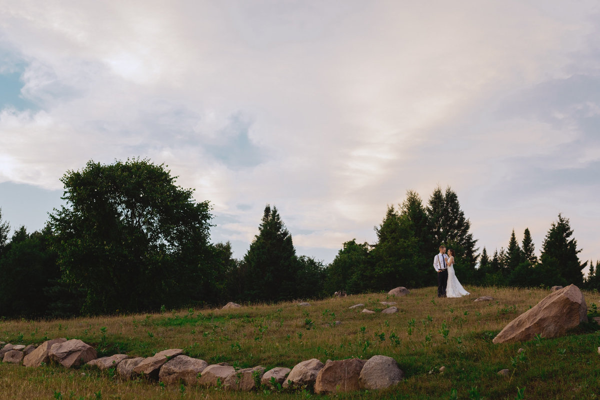 Bride and groom standing on a hill at sunset