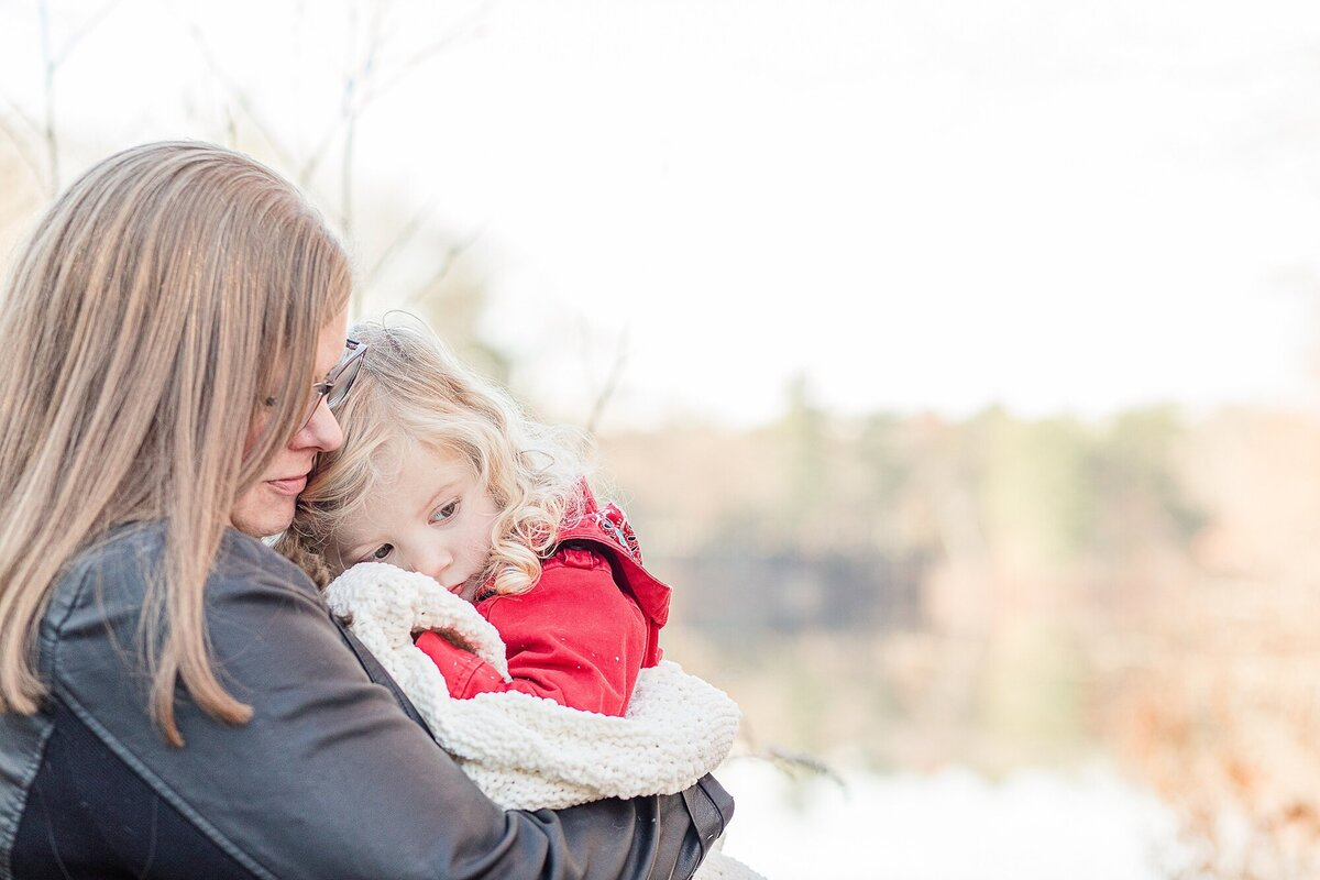 Mother snuggles with daughter in front of water for family photo session in Natick Massachusetts