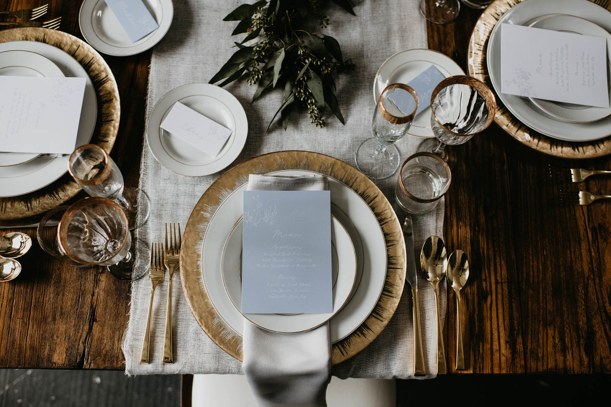 gold plates, white china and grey napkins, gold cutlery  on harvest table