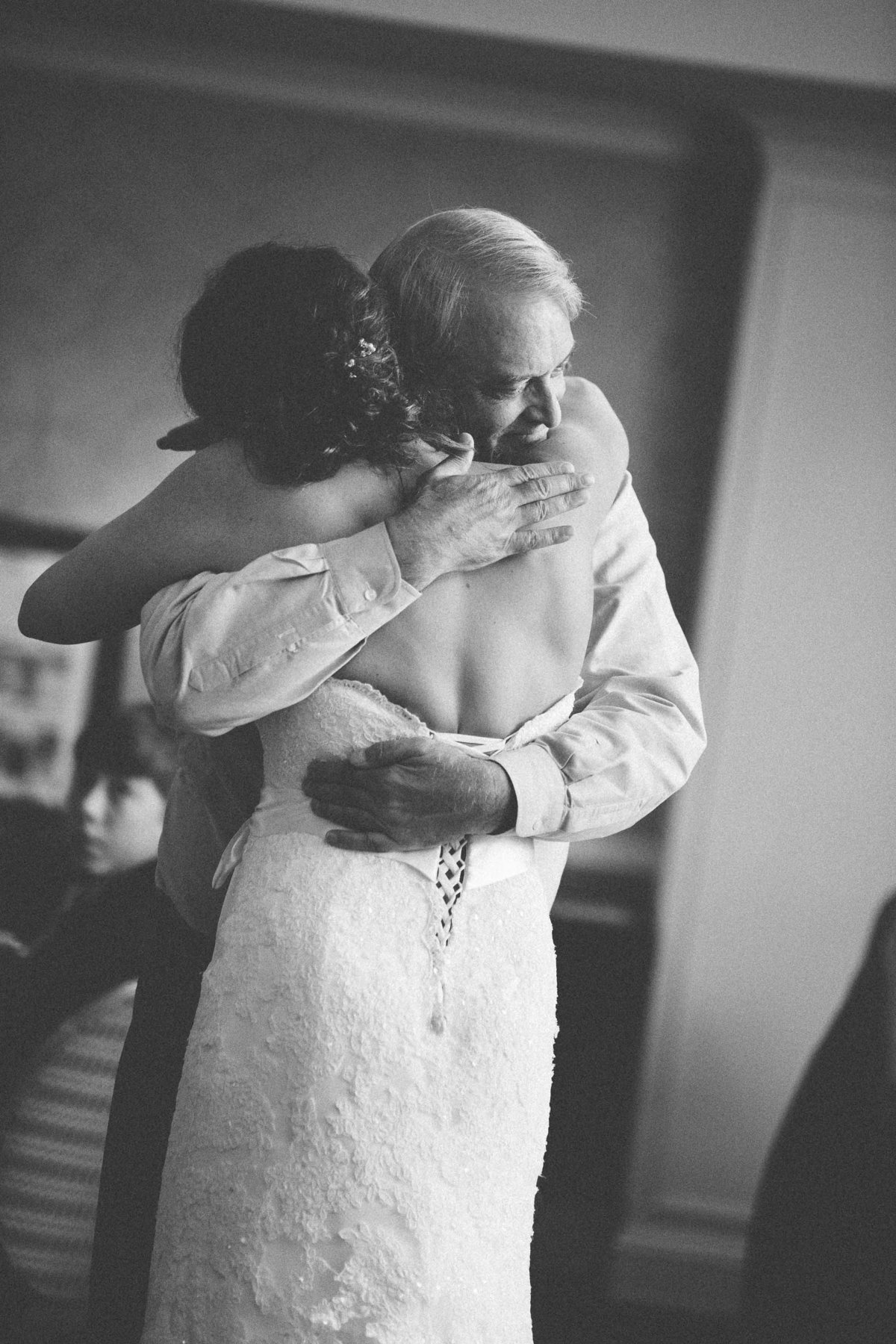 A man hugging a woman in a wedding dress.