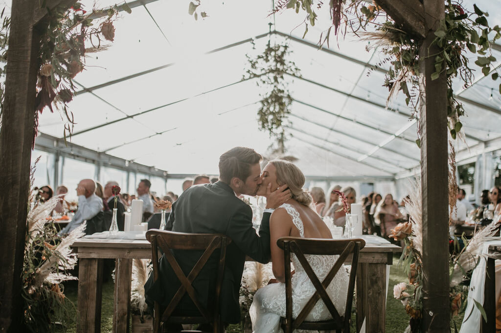 couple kidding inside a clear tent at their wedding reception in front of guests