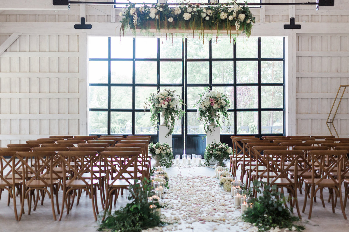 Event design Ceremony decor with white columns, 2 urns and lots of greenery