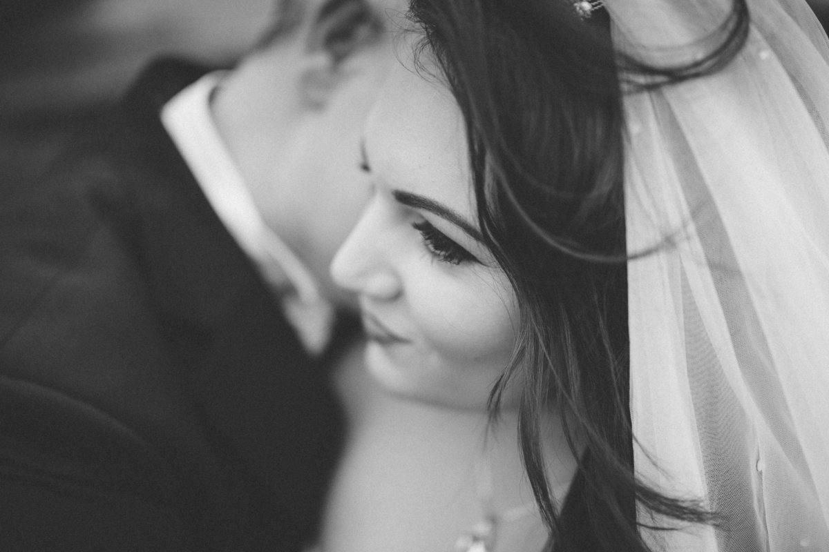 Close up of bride smiling looking over husbands shoulder by Lake District Wedding Photographer Jono Symonds