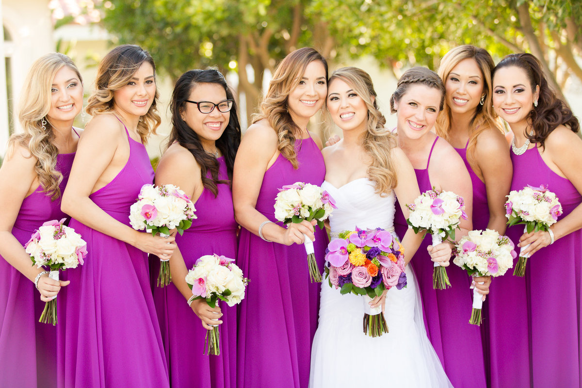 Bridesmaids in their pink dresses on the lawn at villa de amore by matty fran photography