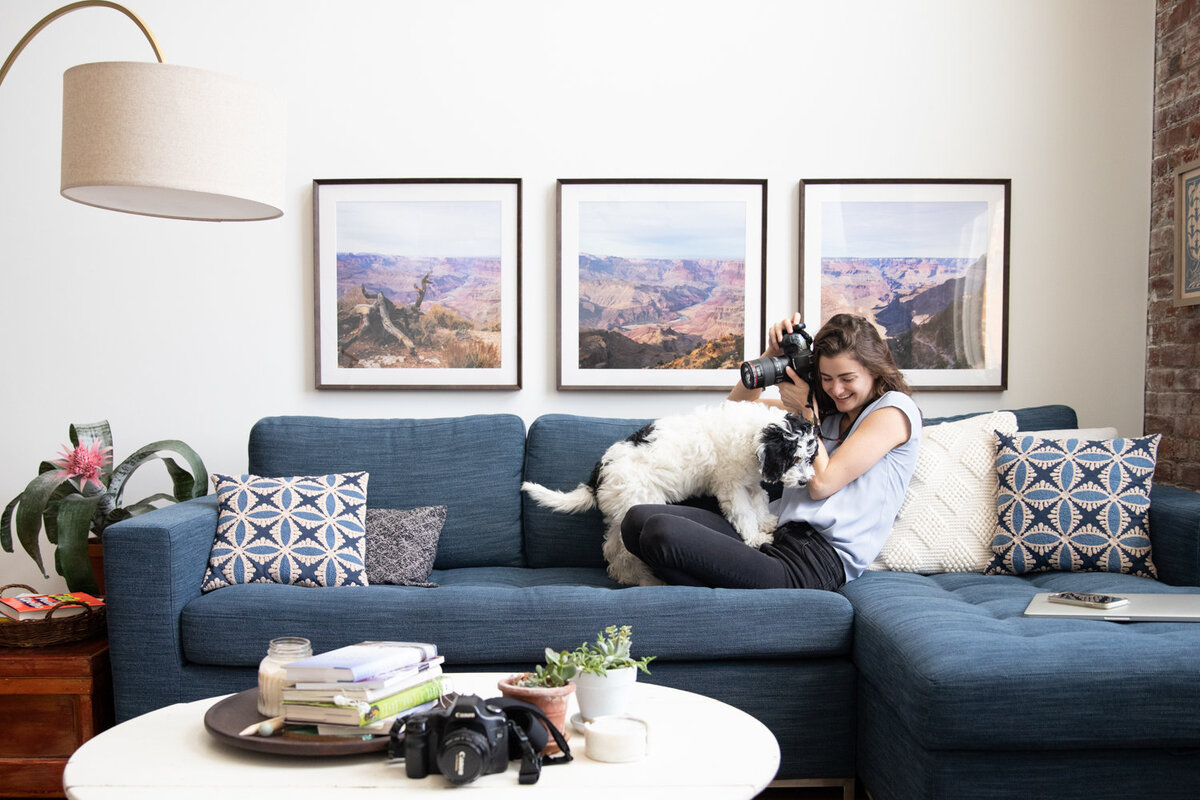 Photographer Laura Volpacchio on couch with camera as her puppy climbs onto her lap.