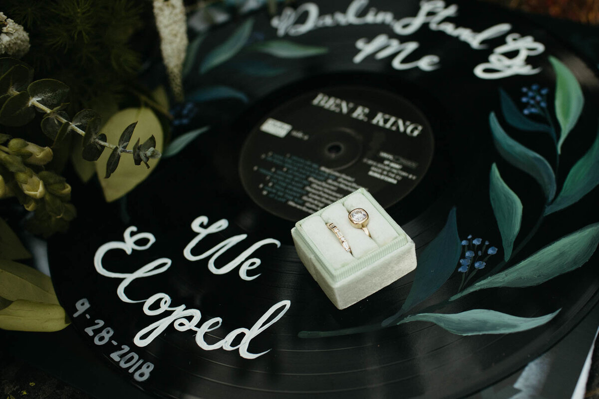 "A vinyl with ""we eloped"" written in cursive in white with flowers painted on it, and a ring box placed on top"