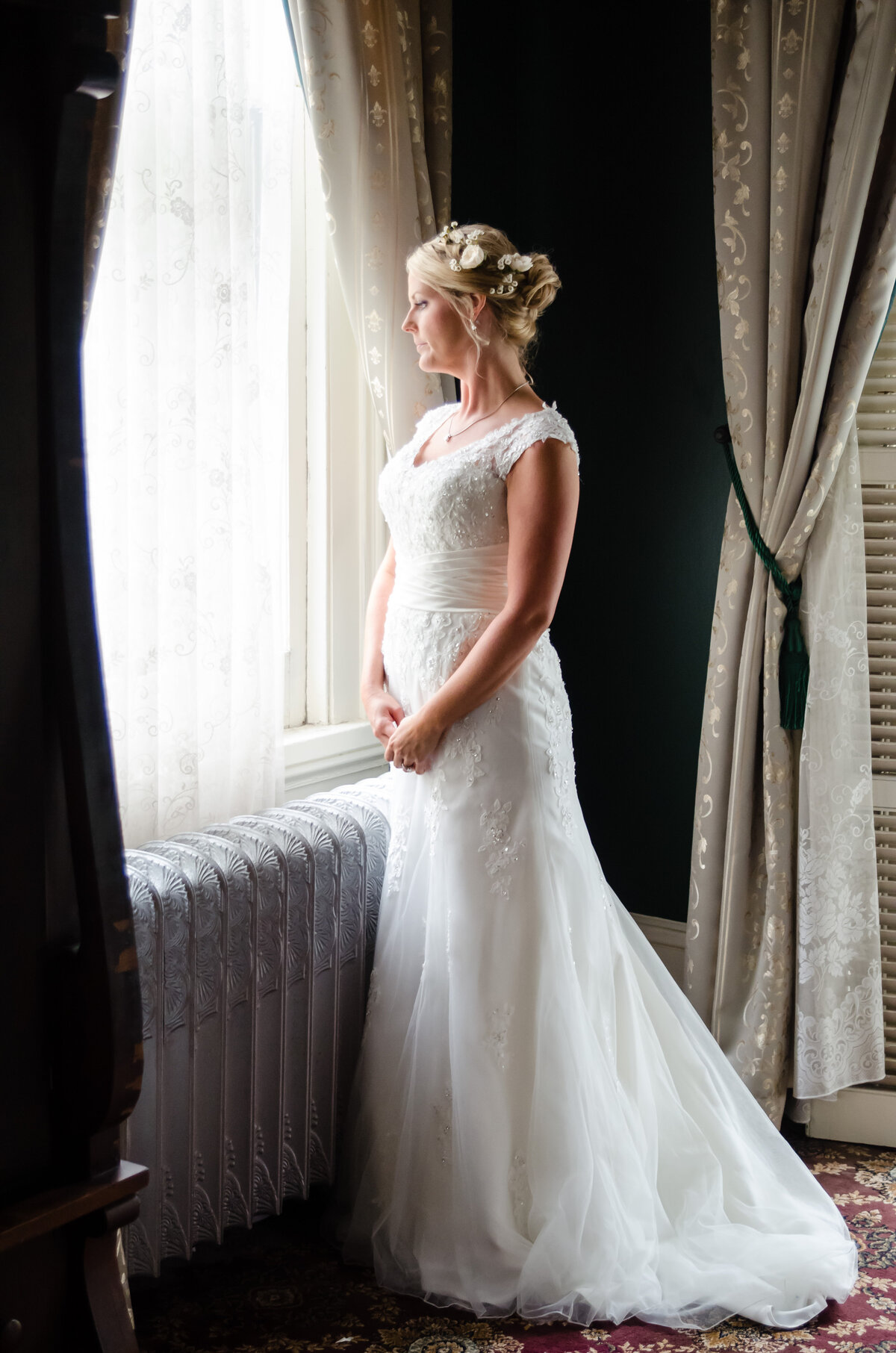 Beautiful bridal portrait photography: Bride gazes out the window of the Columns Hotel on St. Charles in New Orleans, LA