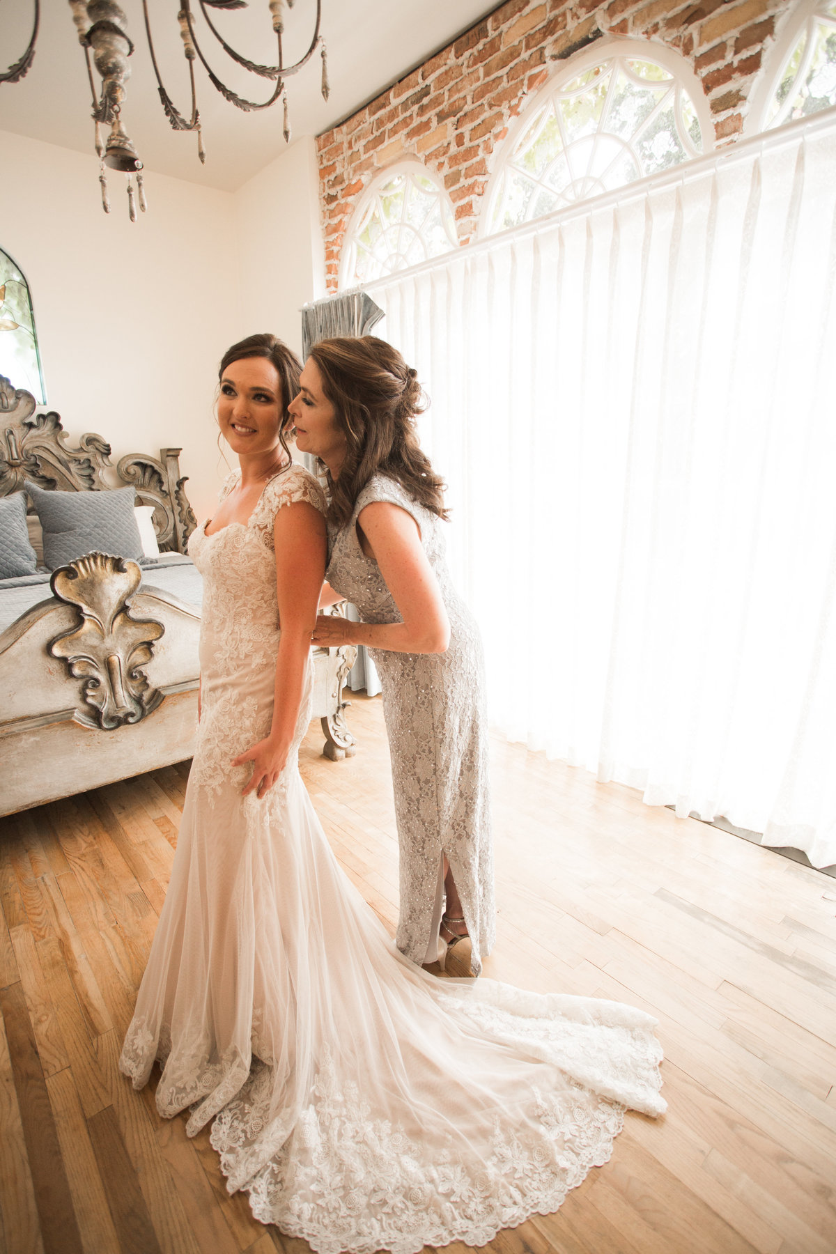 Mother helping bride into dress at 1880 Union Hotel Wedding