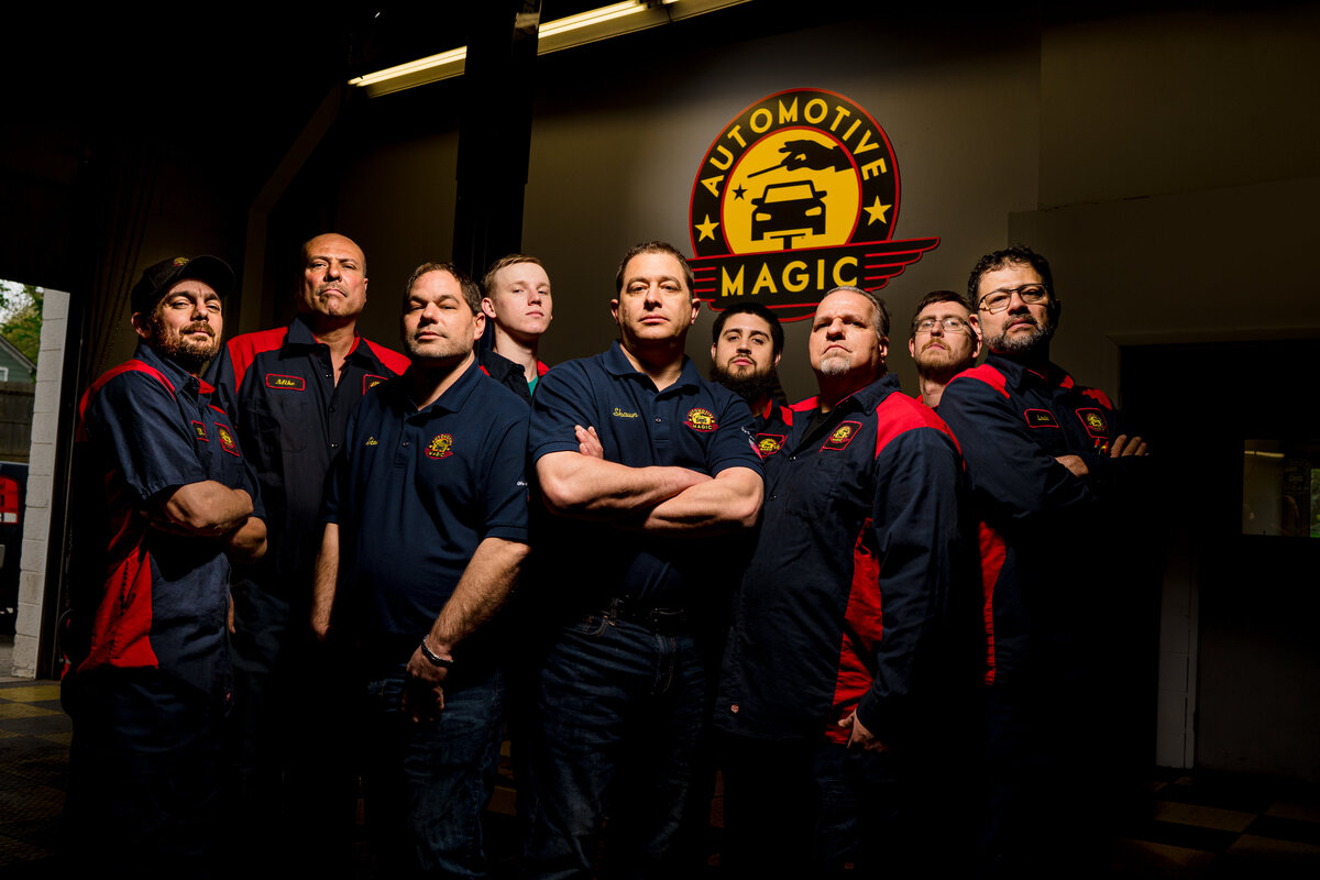 Automotive team poses in the garage of their mechanic garage in front of a sign that says automotive magic