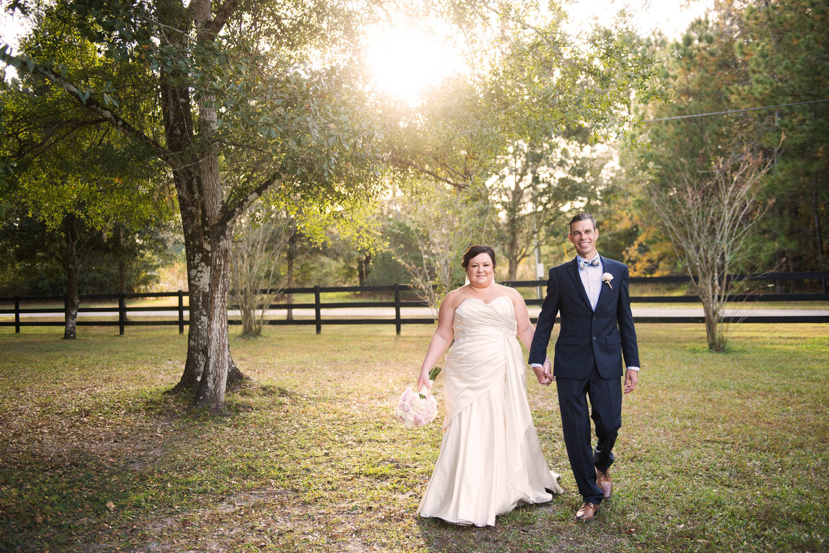 Wedding Photo of couple walking hand in hand at the White Barn