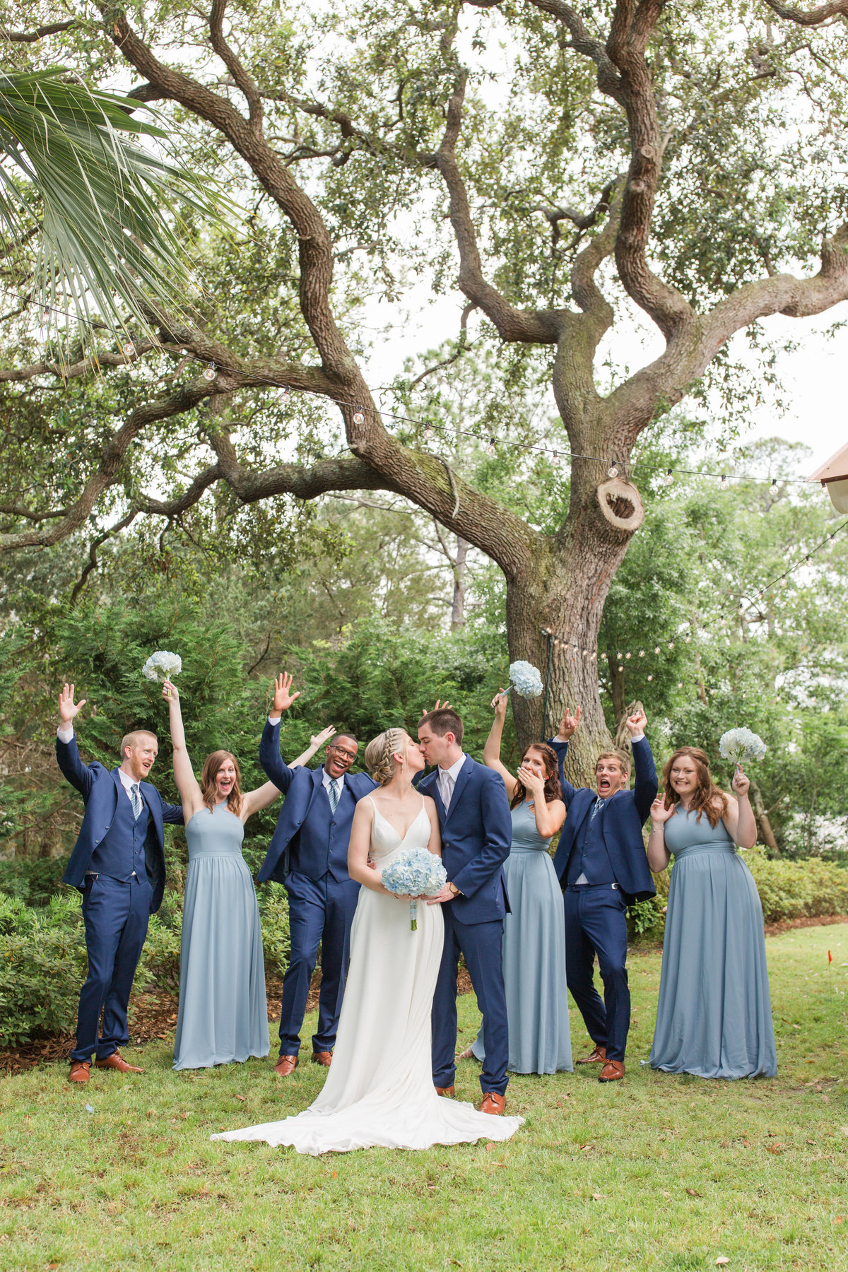 wedding party holding up bouquets and arms while bride and groom kiss