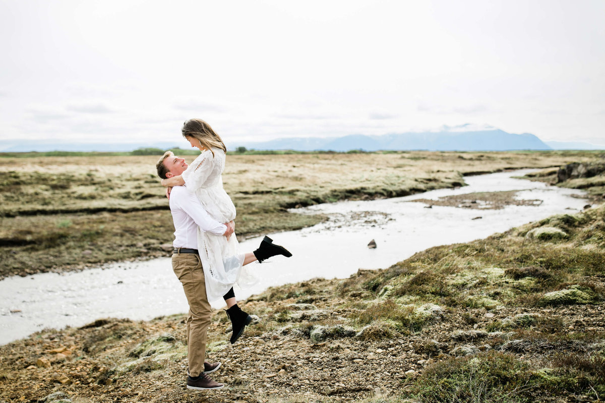 the couple kisses with the rugged iceland river winding behind them
