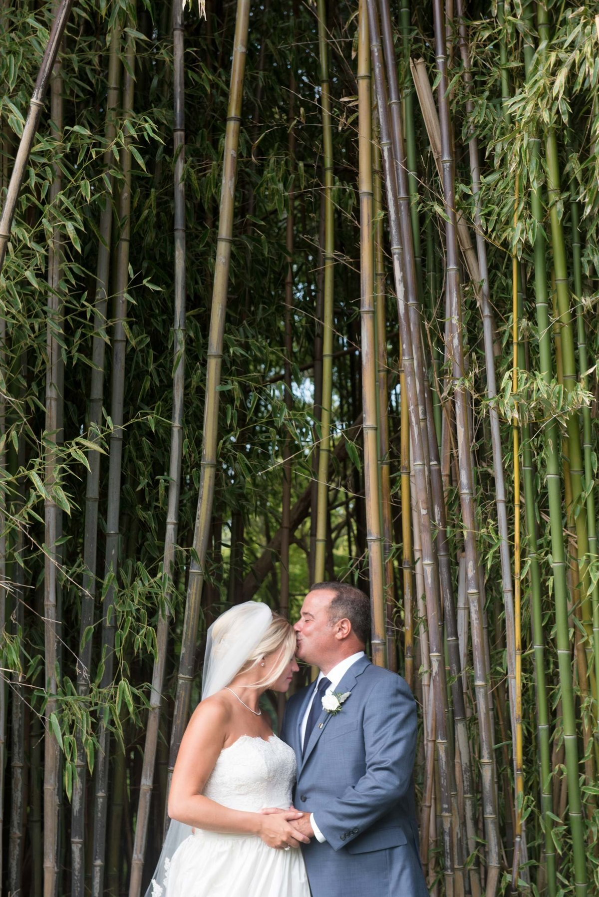 Groom kissing bride outside in front of trees at Huntington Crescent Club