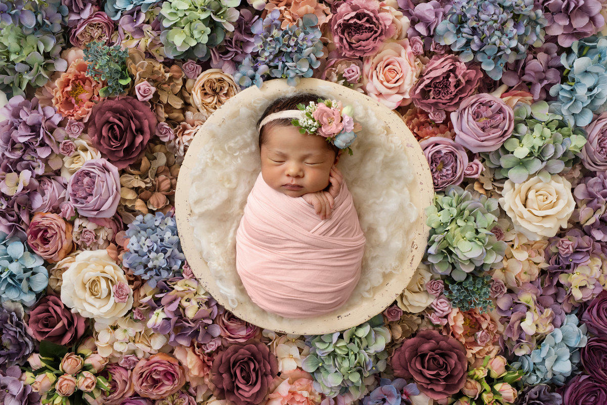 Baby girl in surrounded by flowers