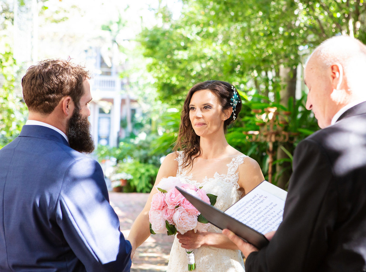 nola destination bride smiles at groom as they say their vows in the courtyard of The Terrell House