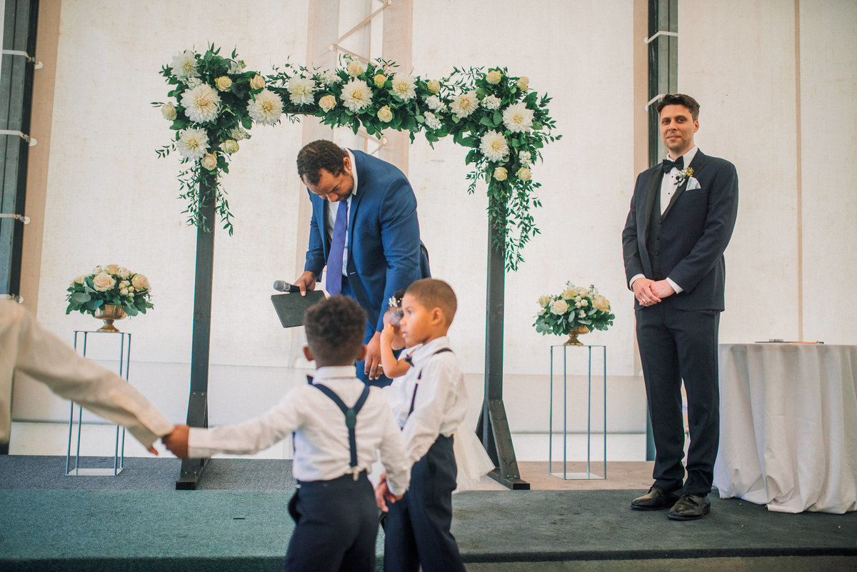 two young ring bearers walk towards the alter