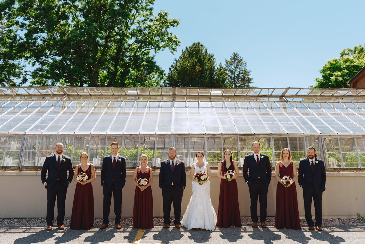 wedding party standing in front of greenhouses
