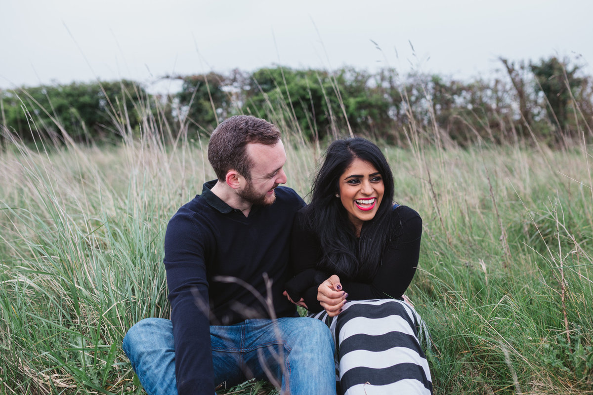 Natural photograph of relaxed couple laughing and cuddling outside sitting in the long grass in the Norfolk countryside
