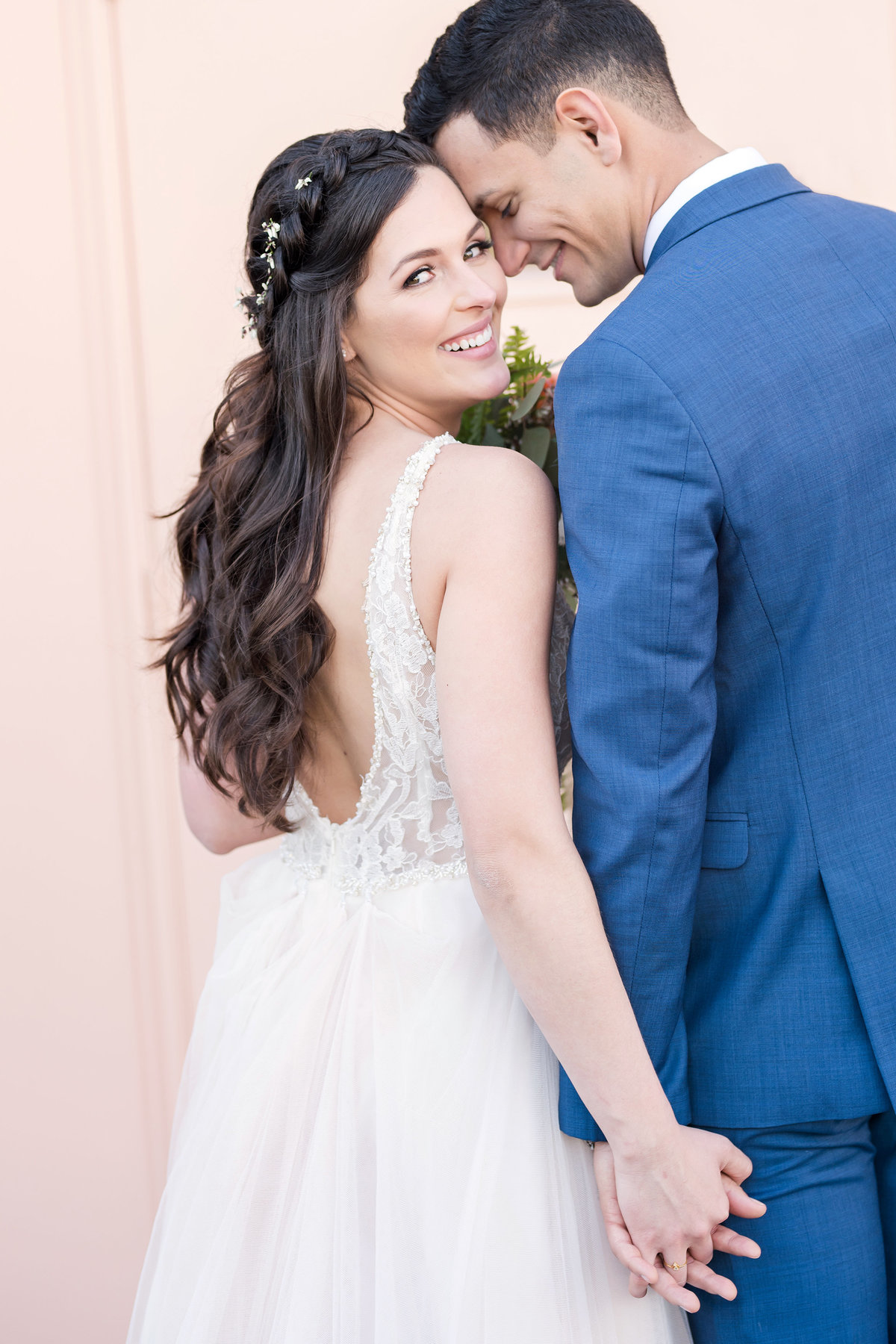 Bride and groom hold hands in front of pink wall and smile looking back over shoulder