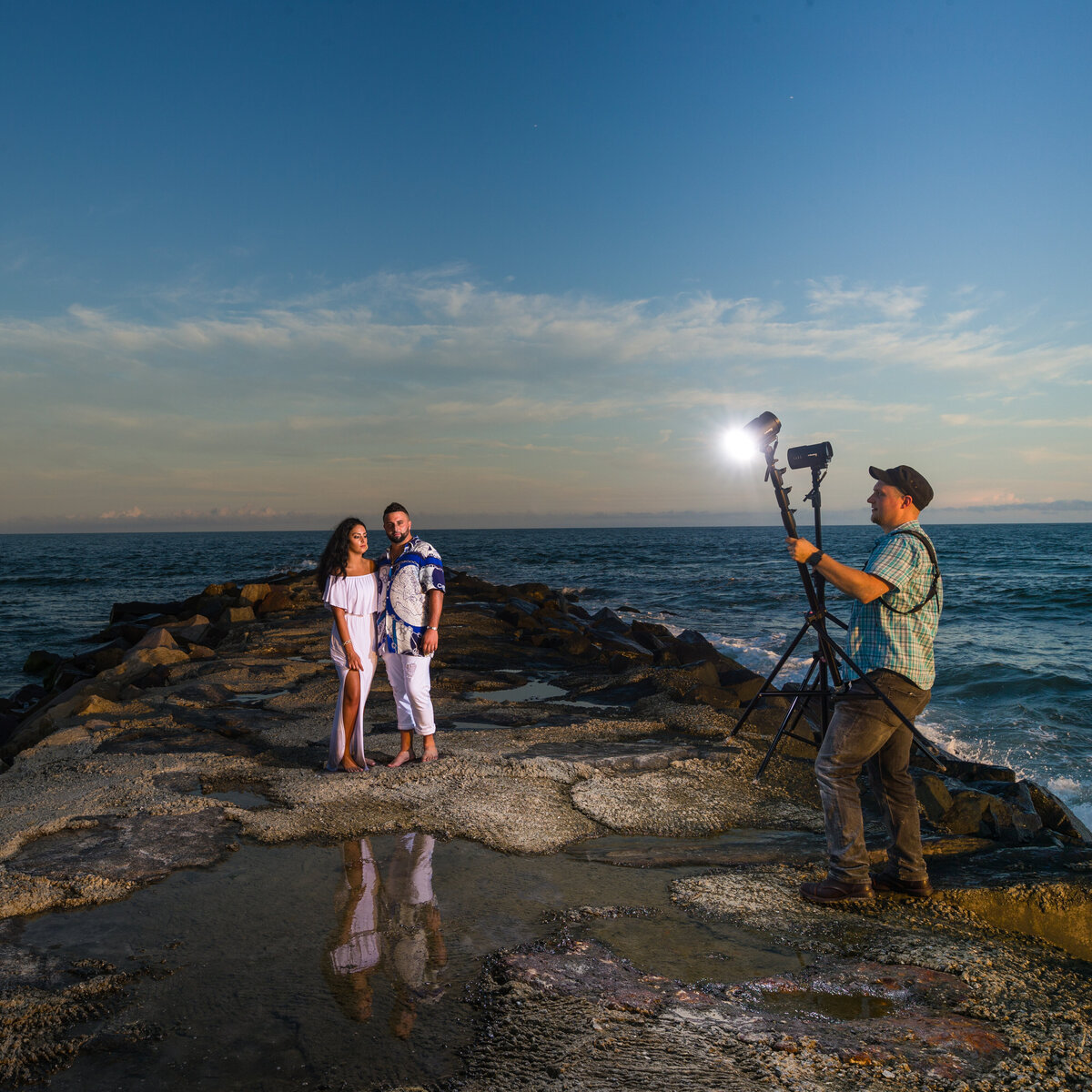 Travis holds profoto lights behind the scenes at a new jersey shore engagement session